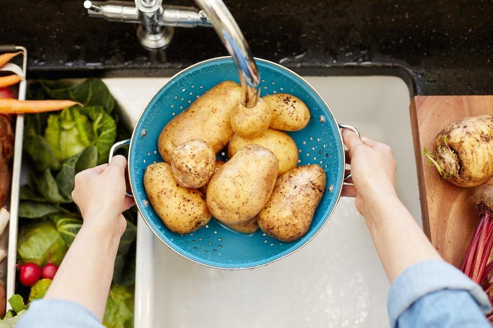Kvinde skyller kartofler