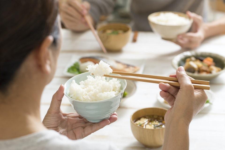 Nainen syö riisiä puikoilla