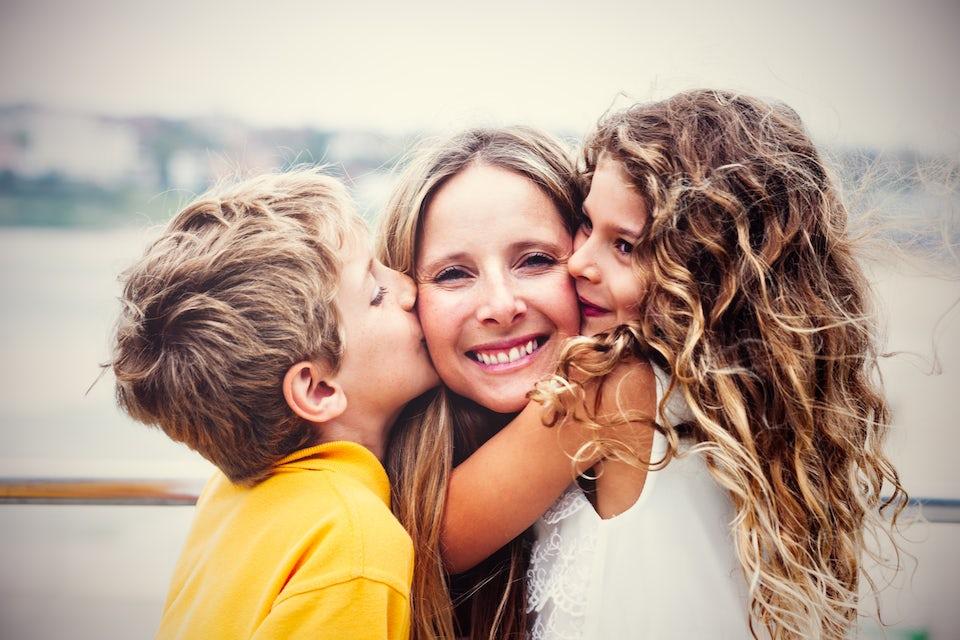 Barn kysser kvinna.