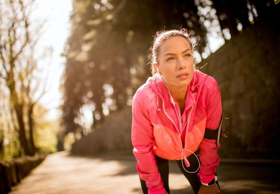 Kvinde på løbetur. Holder pause og står foroverbøjet.