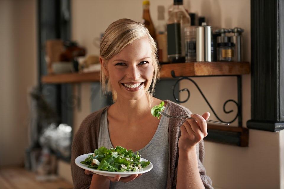 Ung kvinde spiser salat