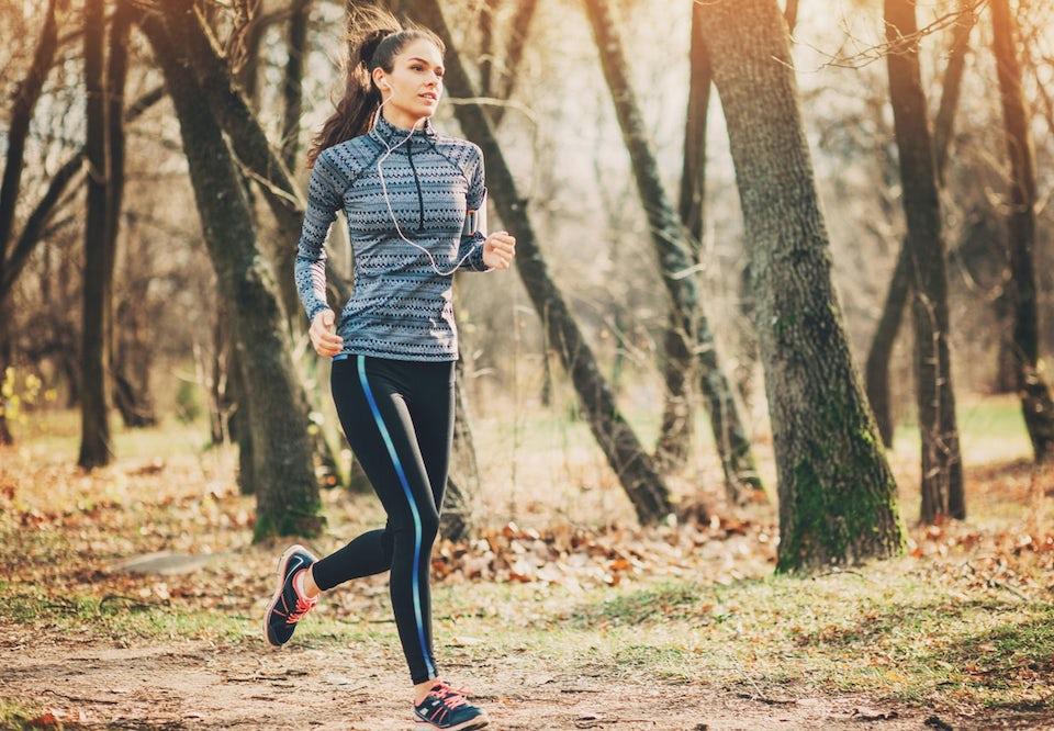 Mørkhåret kvinne løper i skogen. Hører på musikk