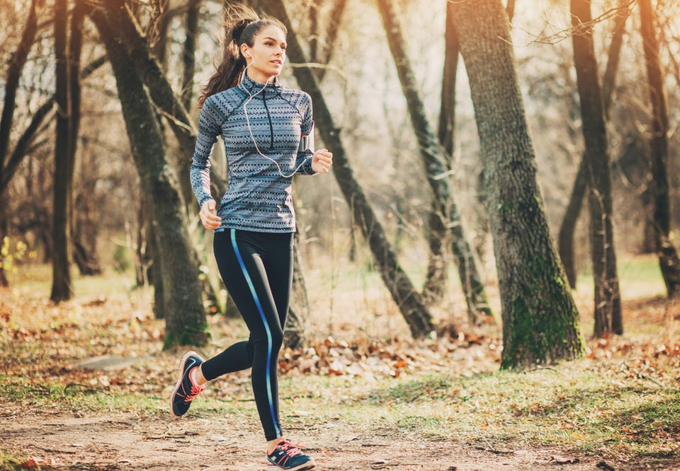 Mörkhårig kvinna springer i skogen. Lyssnar på musik.