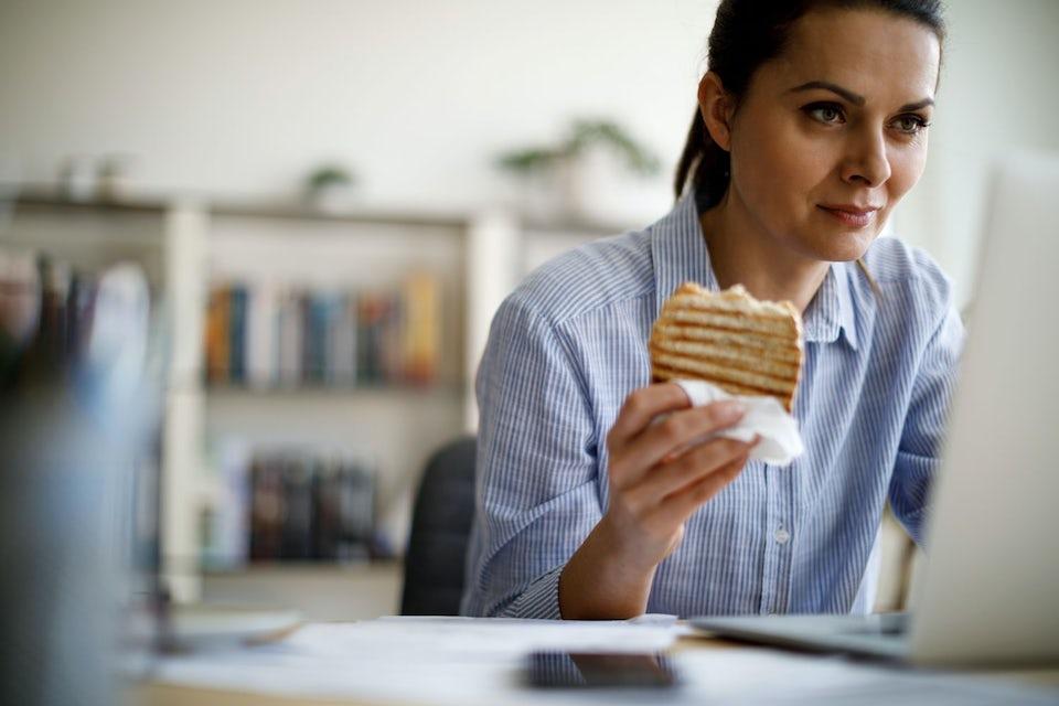 Kvinne som spiser usunt foran PC-en på jobben.