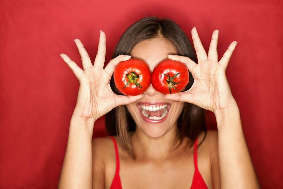 Kvinna håller upp två stora tomater framför ögonen.