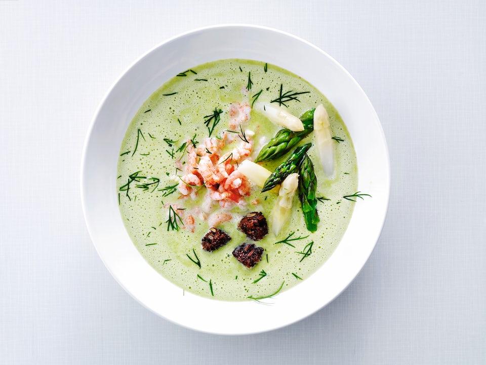 Dyp tallerken med grønn suppe toppet med reker