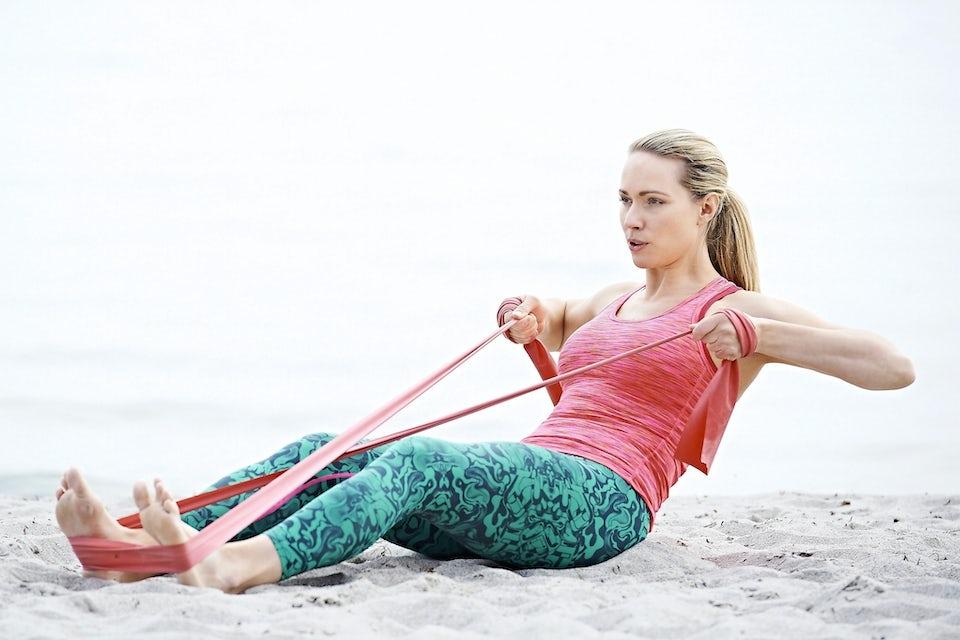 Nainen treenaa jumppakuminauhalla rannalla