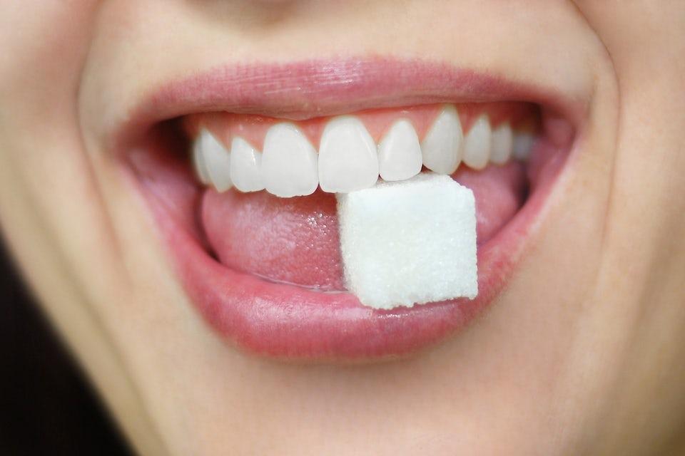 Kvinna äter en sockerbit.