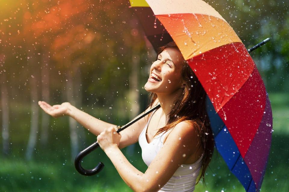 Dame som står i regnet under en fargerik paraply