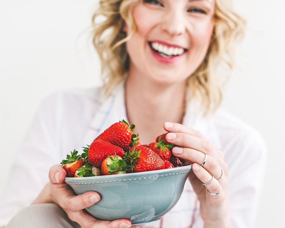 Kvinne smiler bak en skål med jordbær