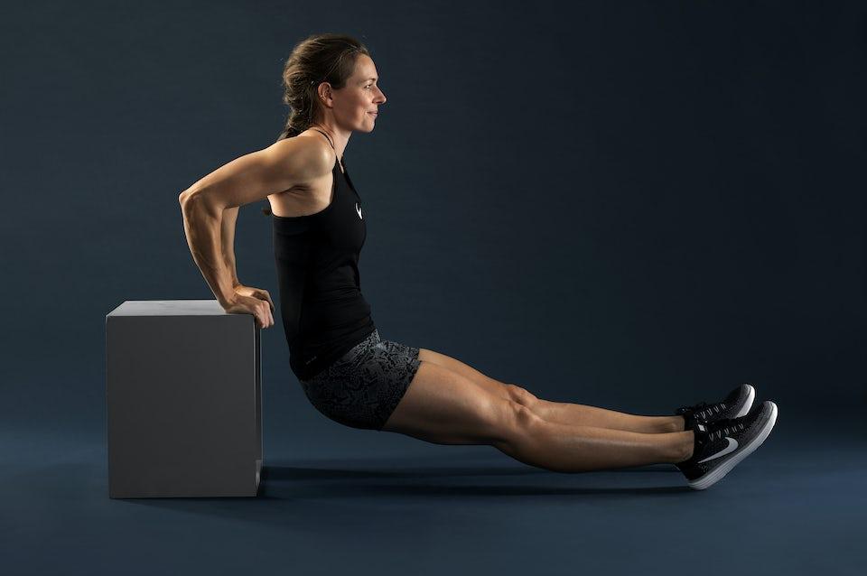 Kvinna gör triceps dips mot trälåda.