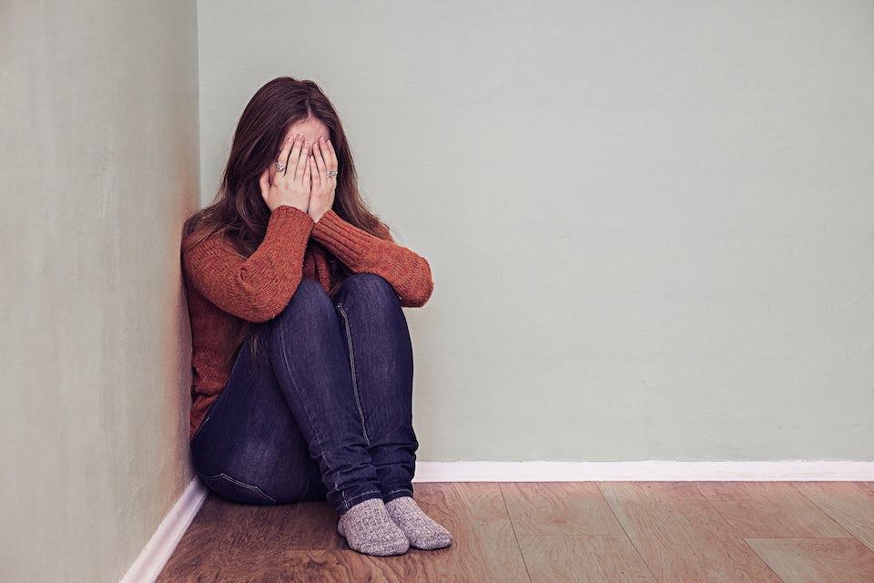 Ångestfylld kvinna gömmer sig i ett hörn