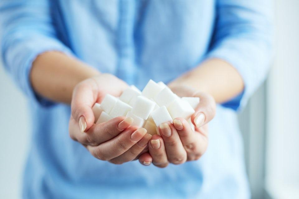 Kvinde, der holder en stor håndfuld sukker