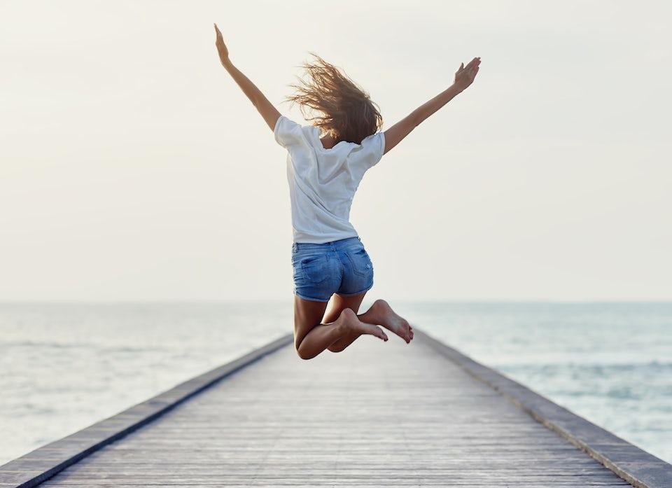 Kvinne med masse energi hopper i lufta på en badebrygge.