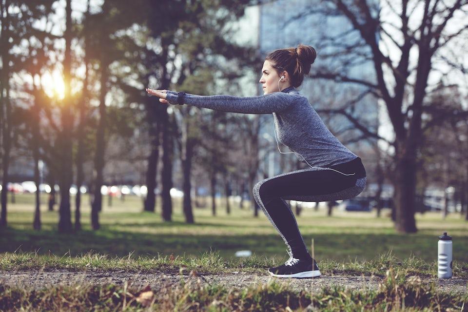Kvinne gjør øvelser utendørs i parken