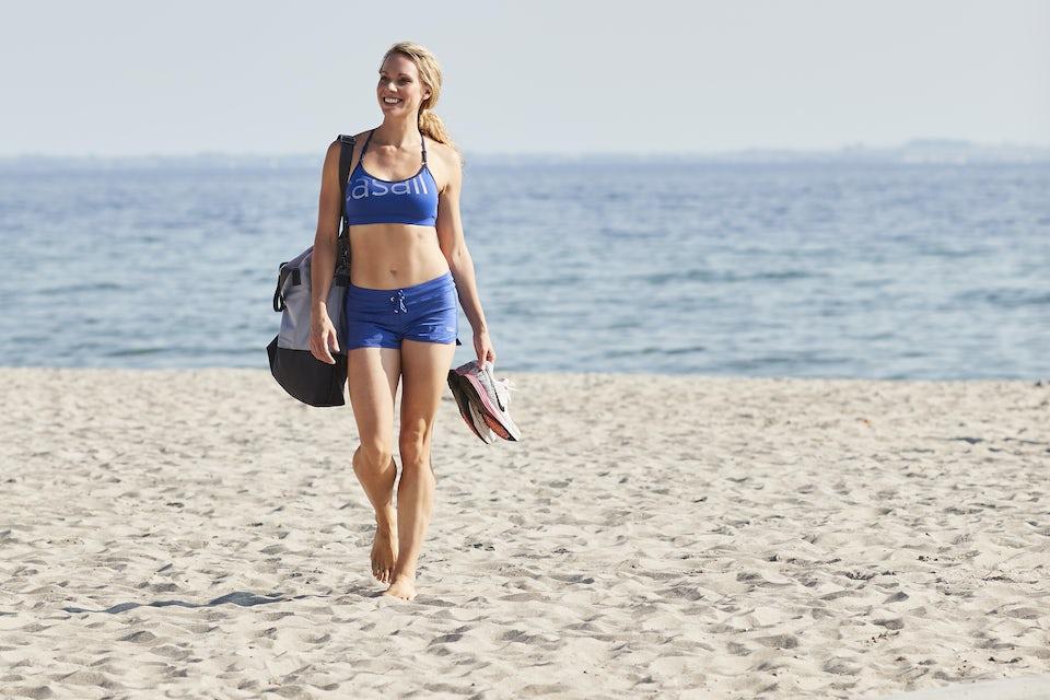 Kvinna på stranden med platt mage.