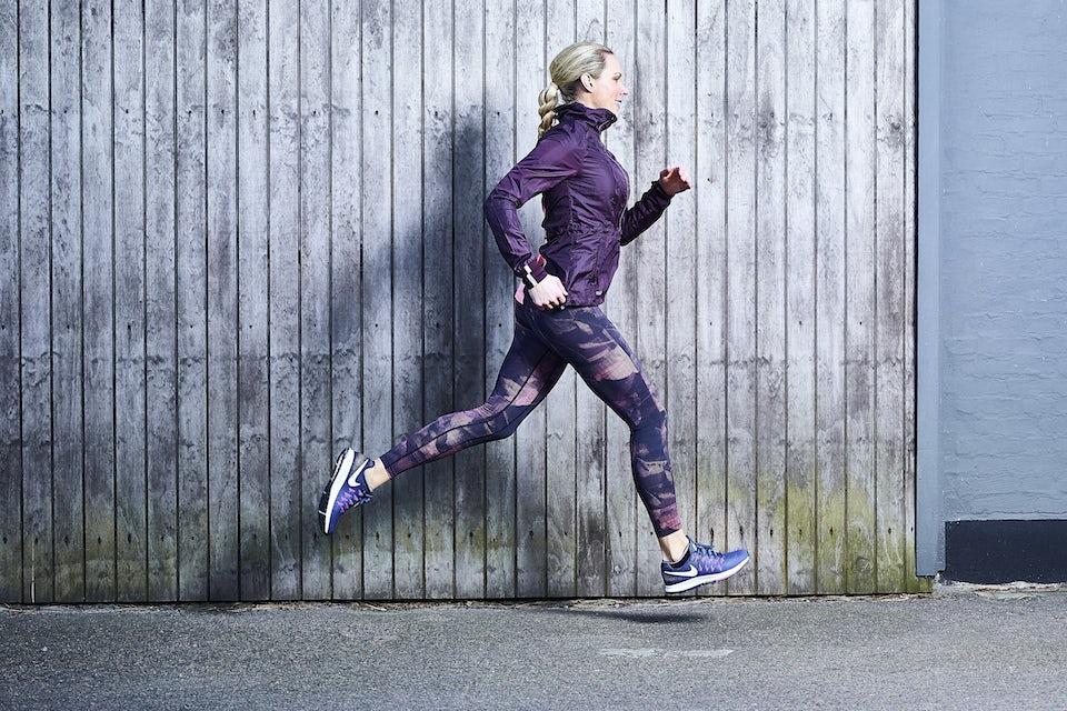 Nainen juoksee lilassa juoksuasussa