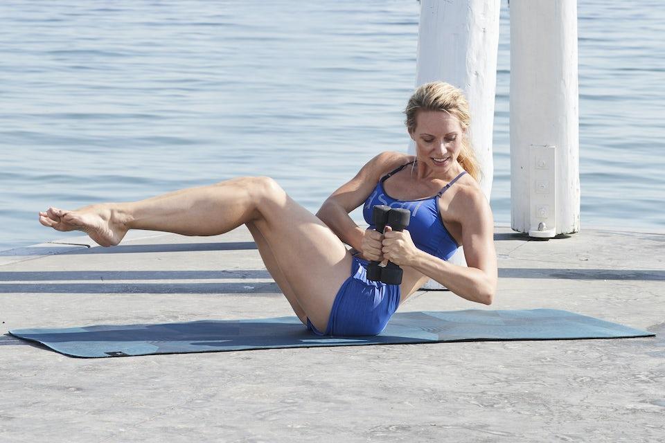 Kvinna gör magövningar på stranden, mycket vältränad.