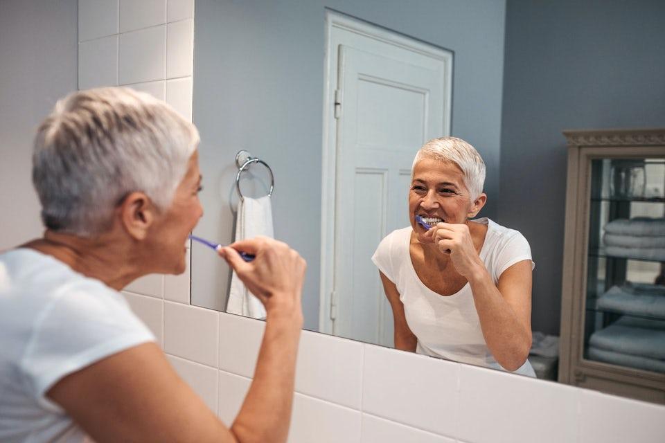 Nainen osoittaa valkoisia hampaitaan