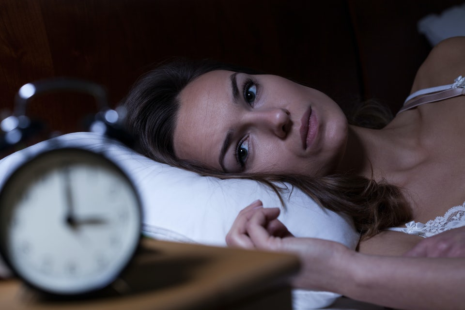 Kvinde ligger i sengen og kigger på ur