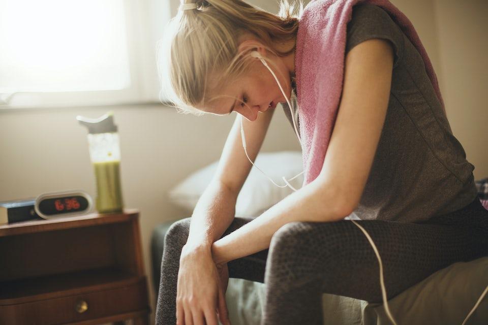 Nainen istuu sängynreunalla treenivaatteissa