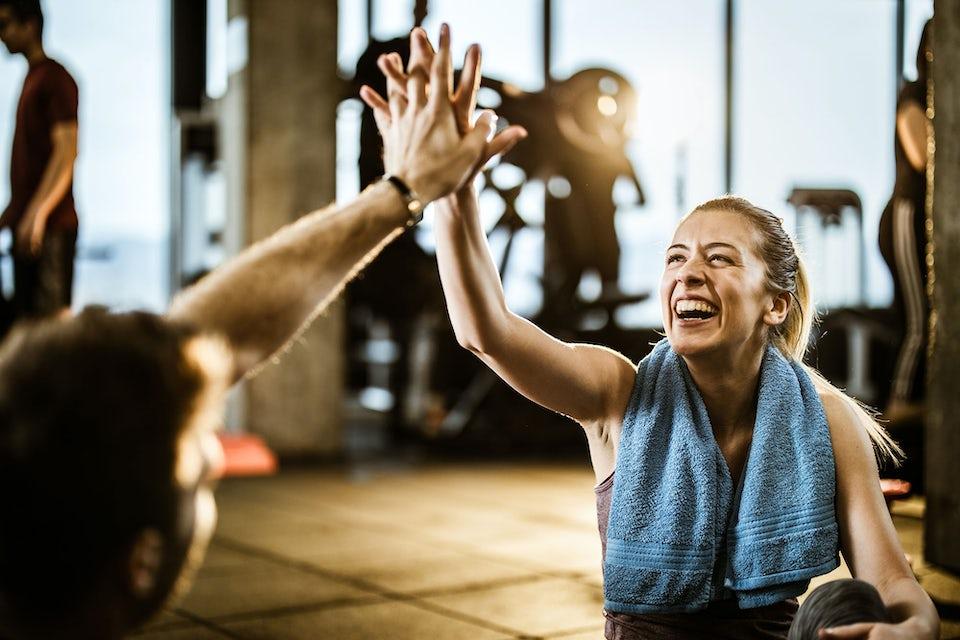 Kvinne og mann tar high five på treningssenteret.