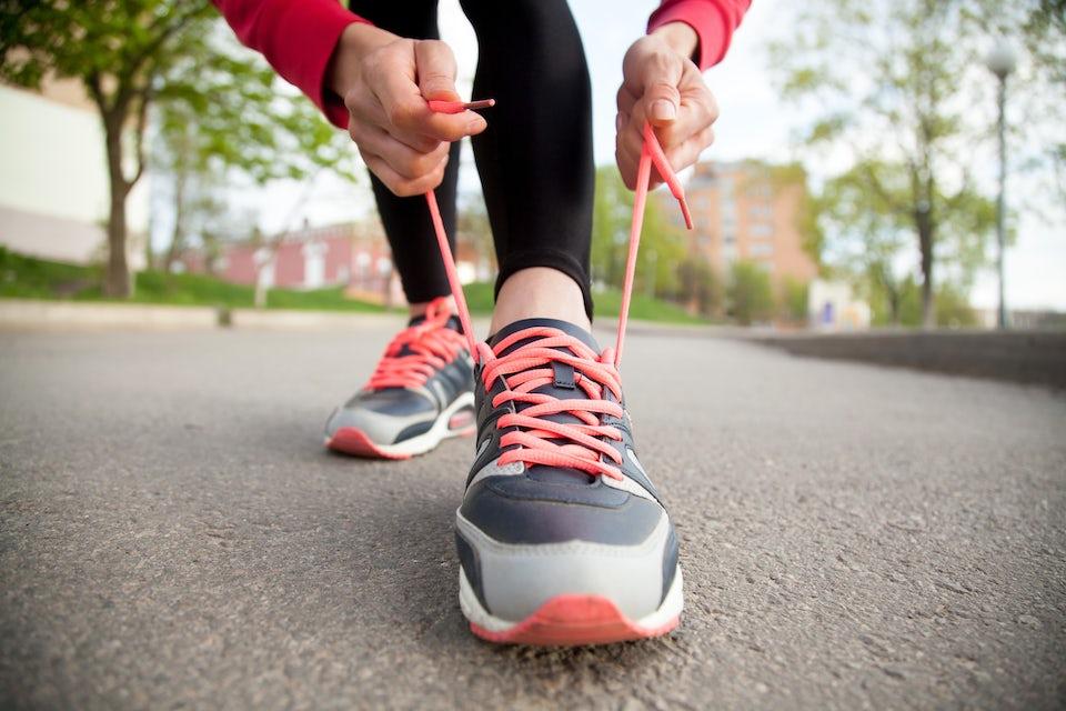 Kvinna knyter skosnörena på löparskor.