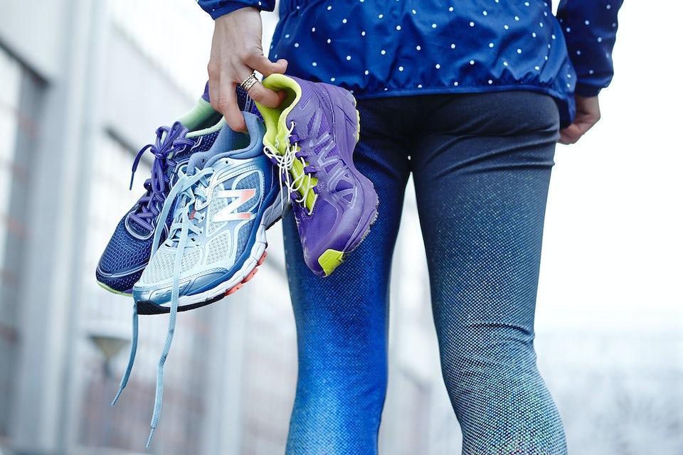 kvinne går med løpesko i hånden