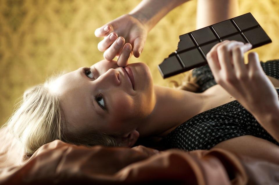 Nainen makaa sängyllä suklaata syöden