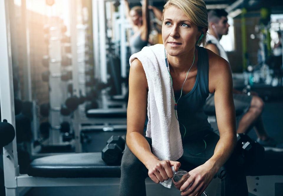 Kvinna sitter på bänk på gymmet.