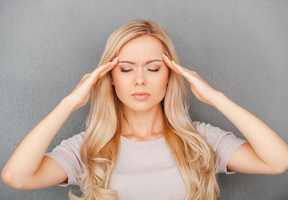 Blond kvinne med lukkede øyne holder seg på siden av hodet med begge hender.
