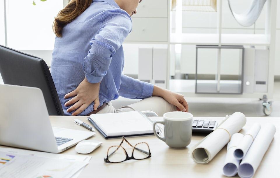 Kvinde har ondt i ryggen, sidder ved computer