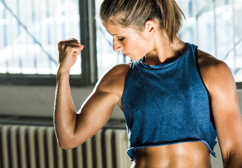 Kvinne spenner sterk overarm mens hun ser på biceps
