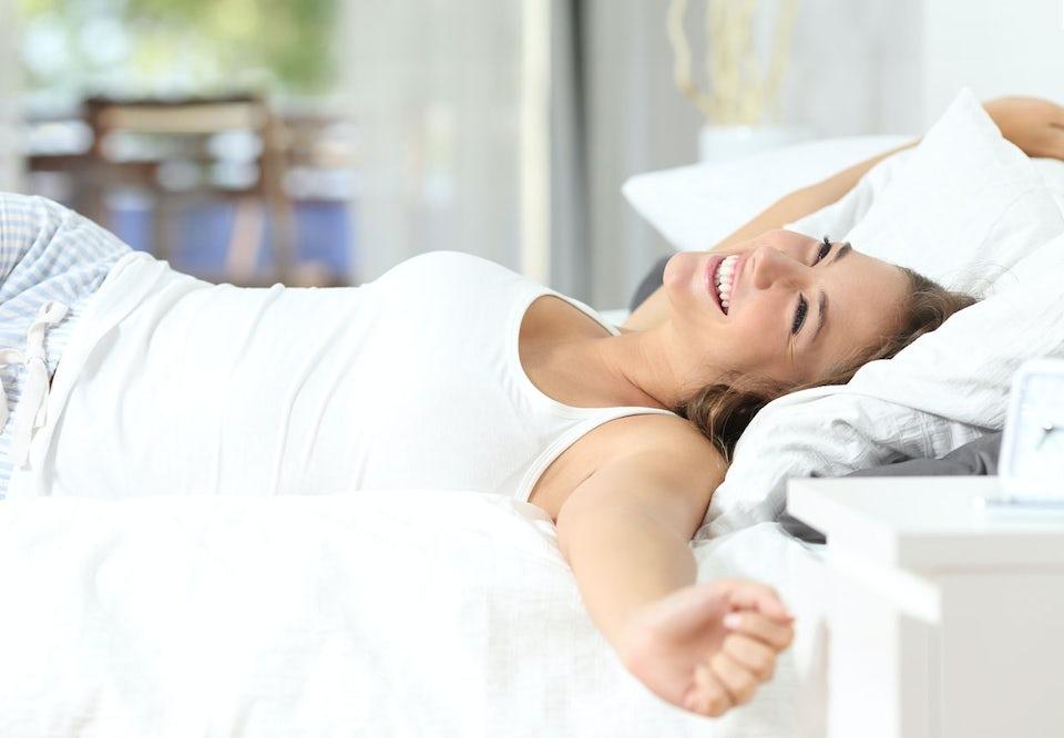 Glad kvinne strekker seg i sengen