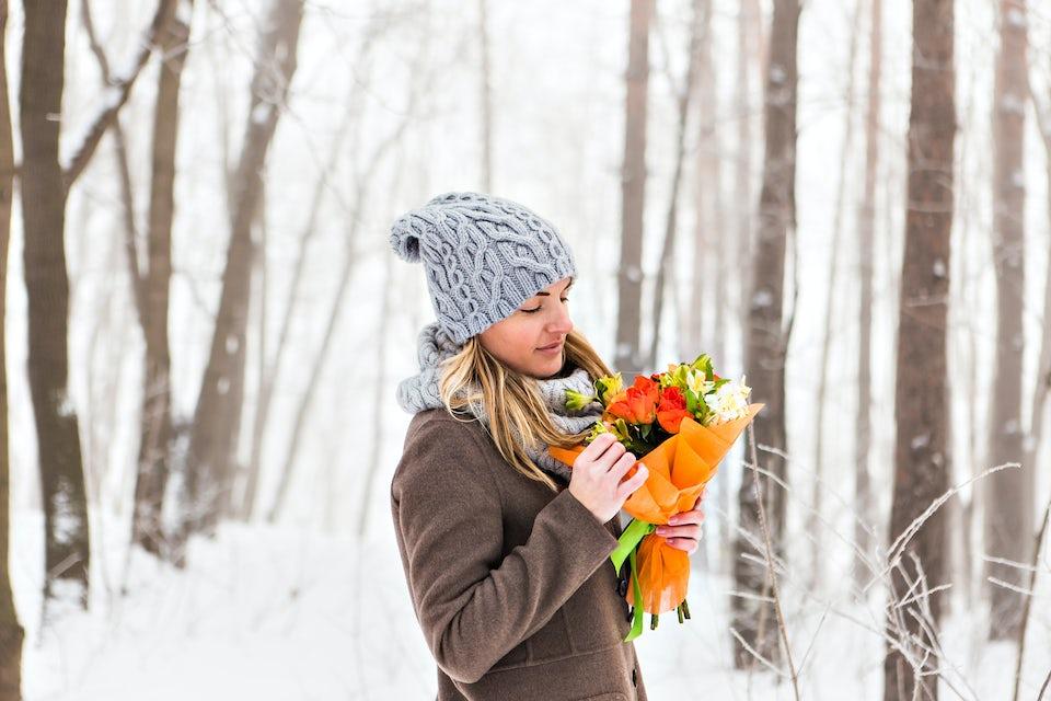 Nainen seisoo metsässä kukkakimppu kädessä
