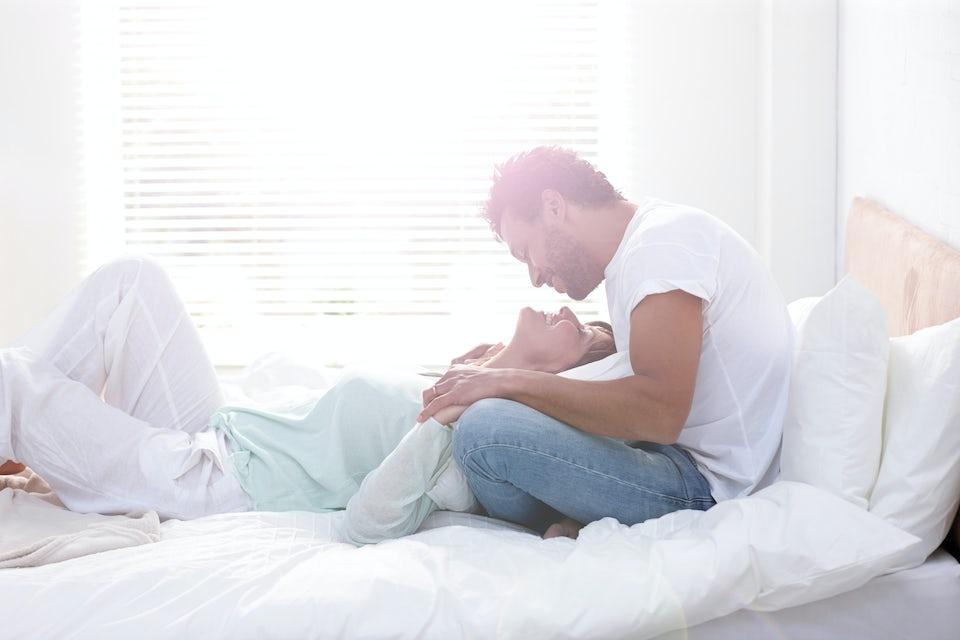 Par smiler til hverandre i sengen