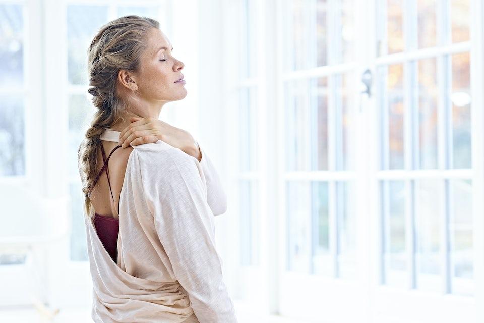 Kvinne har hodepine og masserer nakken