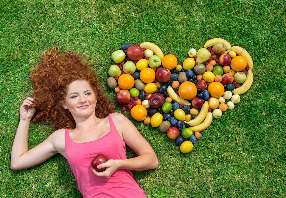 Kvinna ligger på marken vid sidan av ett hjärta som formats av frukter.