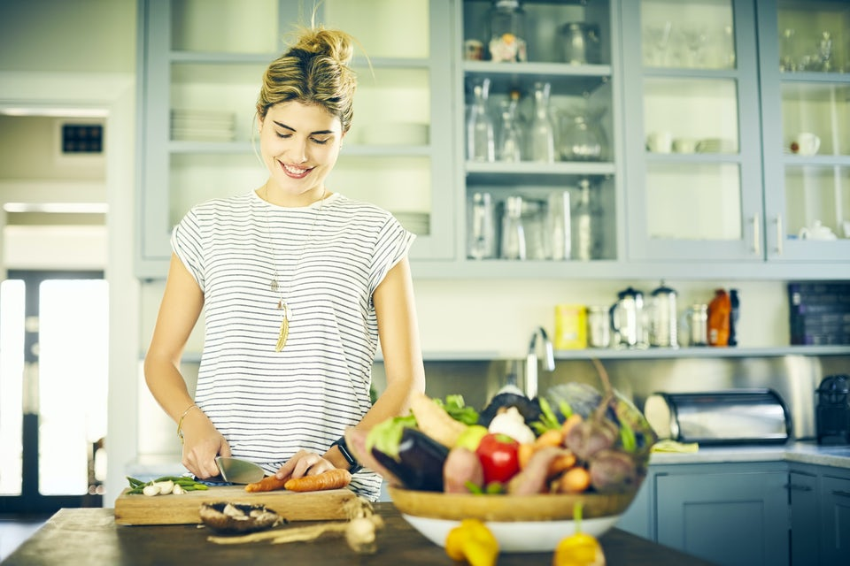 Kvinna skär grönsaker i köket.