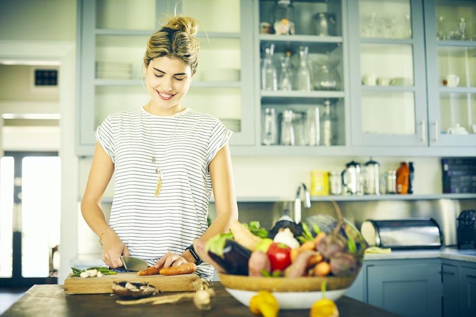 Kvinne kutter grønnsaker på kjøkkenet