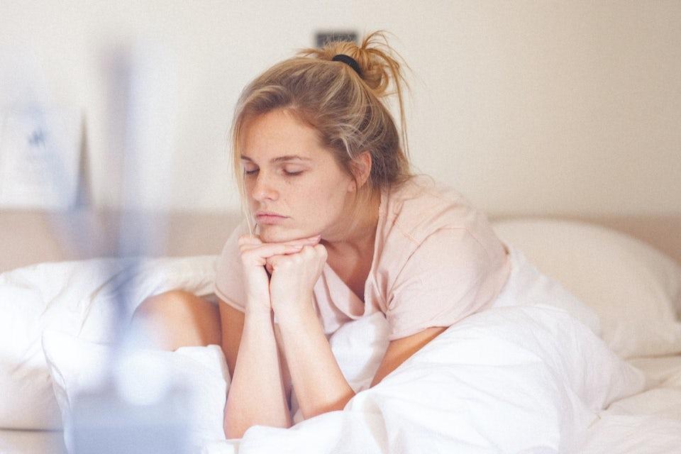 Træt kvinde gaber foran sin computer på jobbet.