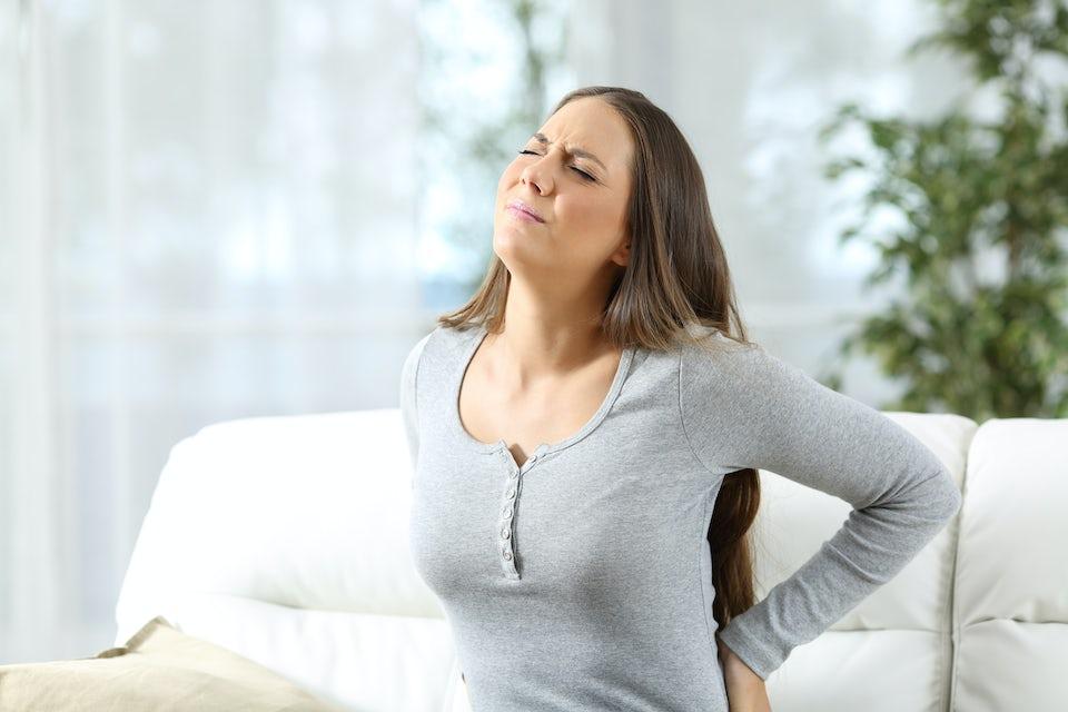 Kvinne med smerter i ryggen