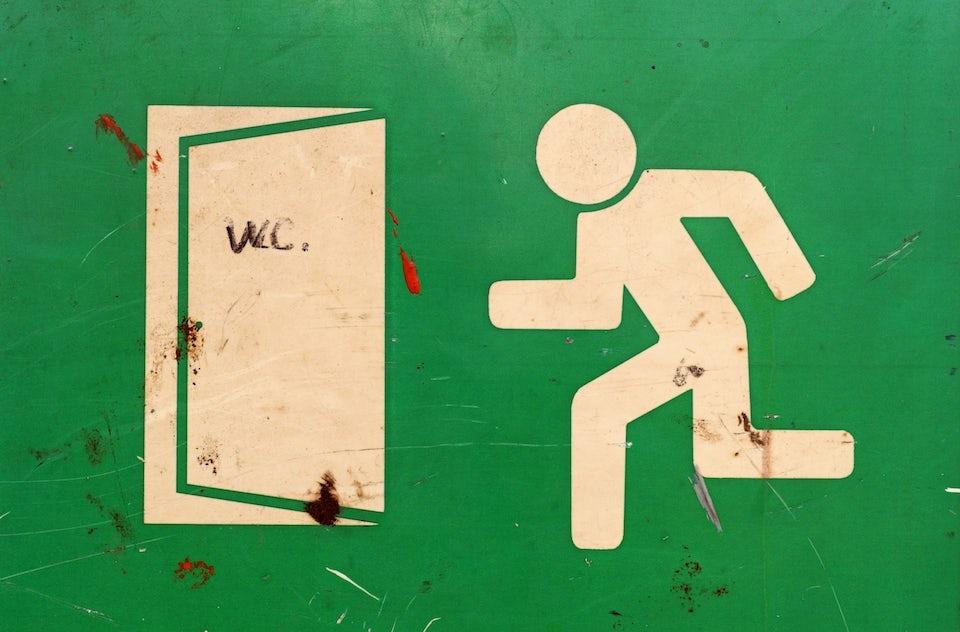 Klassisk grön skylt som visar på nödutgången är omgjord till toalettskylt.