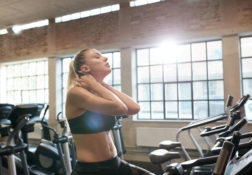 Kvinne på treningssykkel har lukkede øyne og vondt i nakken
