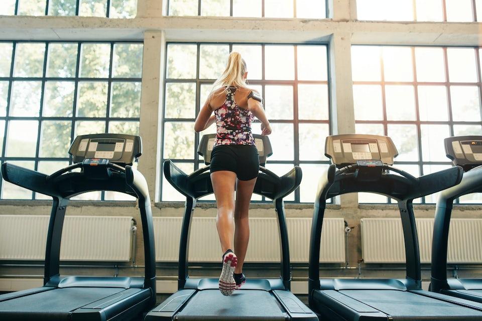 Kvinna springer på löpband.
