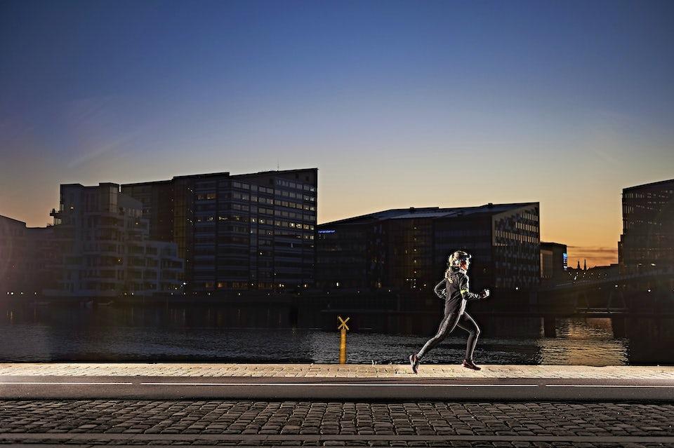 Kvinna springer i mörker.
