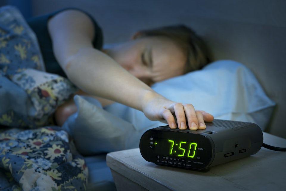 Nainen laittaa herätyskelloa pois päältä sängyssä