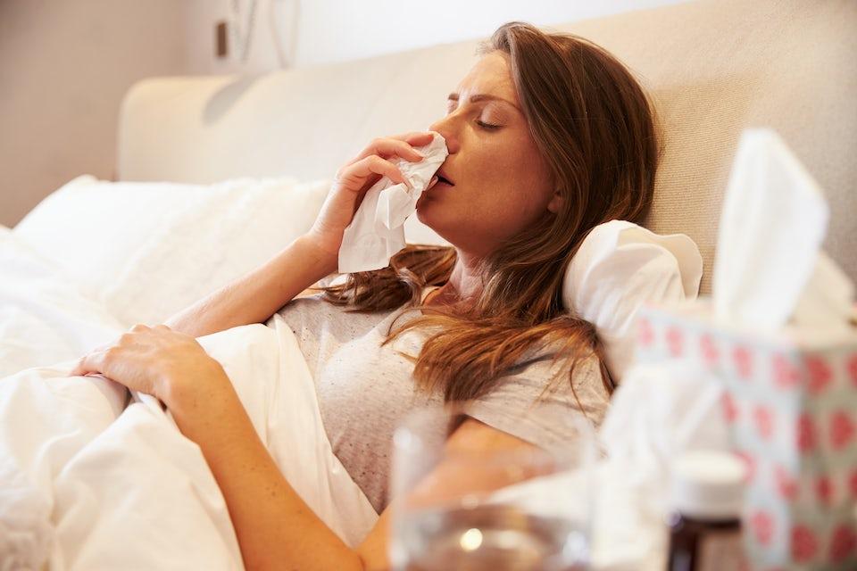 Förkyld kvinna i sängen.