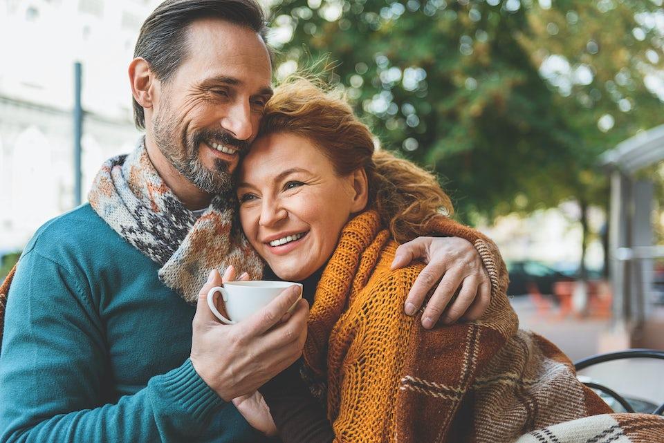 Par sitter på kafé og smiler