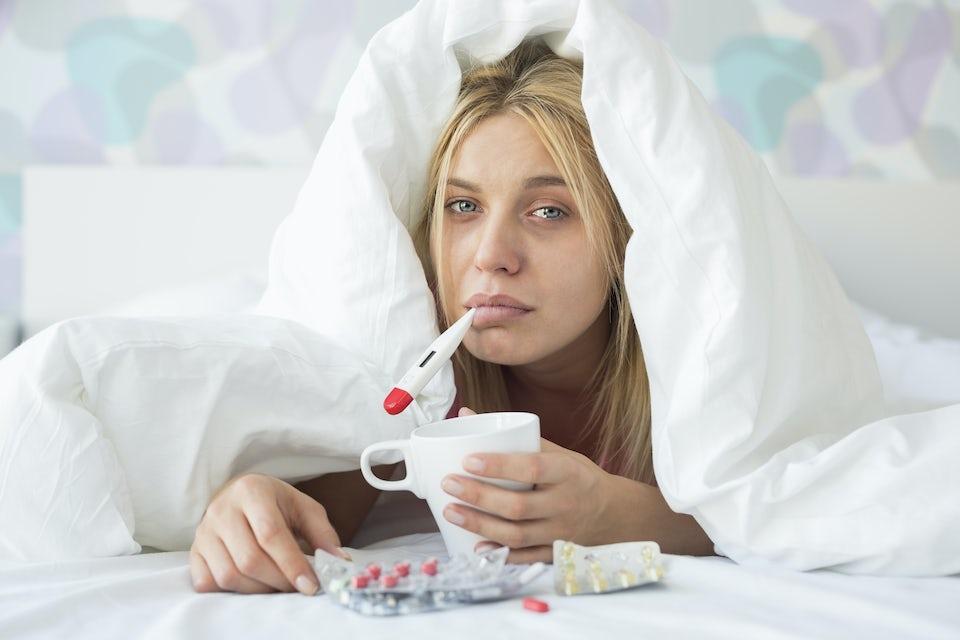 Kvinna ligger i sängen med en febertermometer i munnen.